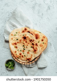 Fresh naan bread on gray cement background with copy space. Top view of several perfect naan flatbreads. Vertical