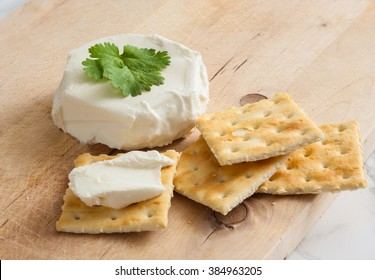 Fresh, natural cream cheese with crackers on a wooden cutting board.
