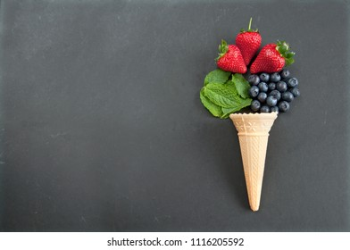 Fresh natural flavors pouring out of an icecream cone including strawberry, mint and blueberries