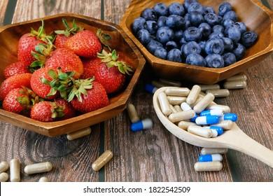 fresh natural fruits vs pills. Natural vitamin in fruits vs synthetic vitamin in pills. Choice between natural and synthetic way of health care. Alternative medicine.