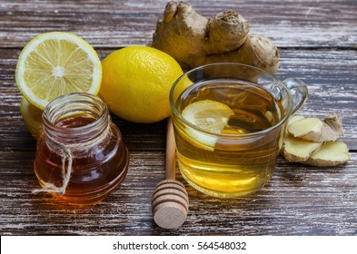 Fresh natural ginger herbal tea in a glass cup on wooden table.Alternative remedies to treat cold and flue: ginger, lemon, honey and spice.Traditional medicine and natural health care concept