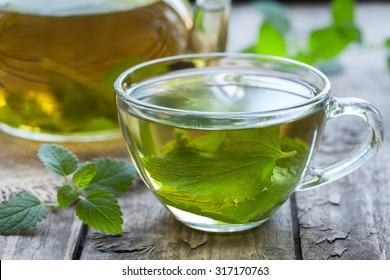 Fresh natural green melissa herbal tea in glass cup. Organic aromatherapy relaxation medical healthy beverage. Rustic wooden table background. Rustic style natural light.