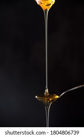 Fresh natural honey Flowing on a black background spoon.
