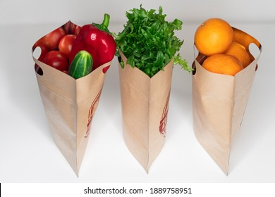 Fresh natural vegetables and tangerines in paper bags for storage with a zipper. Reusable packaging without plastic, zero west concept.