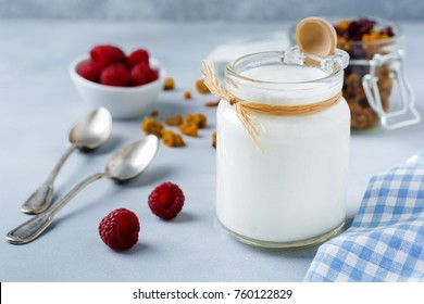 Fresh natural yogurt in a glass jar on  gray concrete or stone background.Healthy foodfor breakfast. Milk dairy product. Selective focus.