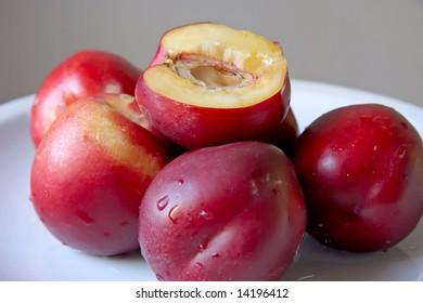 Fresh nectarine fruits whole and cut on white plate
