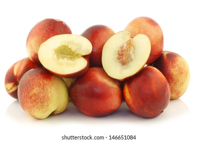 fresh nectarines and a cut one on a white background