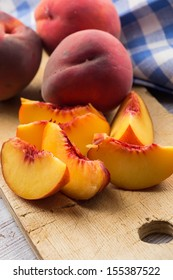 Fresh nectarines on wooden board whole and sliced. Selective focus.