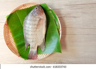 Fresh Nile Tilapia fish put on banana leaf on threshing basket with wood table background topview