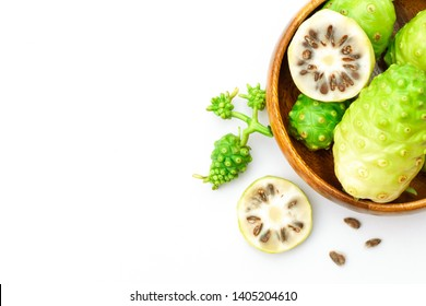 Fresh noni fruit or morinda citrifolia(commom name as indian mulberry, cheese fruit) and slices in wood bowl isolated on white background. Copyspace for text and content. Top view.