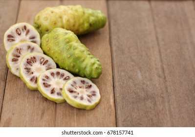 fresh noni fruit and noni slice on wooden background and space.slice of noni fruit with space on wooden background.