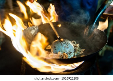 Fresh Noodles prepared in a Wok on open fire at a Street food Restaurant on Yaowarat Road, Bangkok, Thailand.