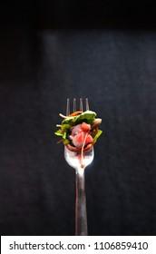 暗い背景に新鮮なタコのカルパチオと柑橘のホウレンソウサラダペスト、銀のフォークのバルサミックなドレッシング