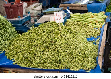 Fresh okra, also known as lady fingers, stacked in a pile at market stall at weekly farmers market in Yenifoca. Green vegetables, vegan and vegetarian food. Indian, middle eastern cuisine.