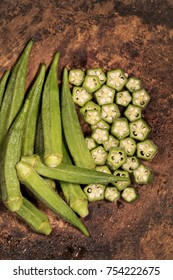 Fresh okra plant lies on a cutting board in the kitchen