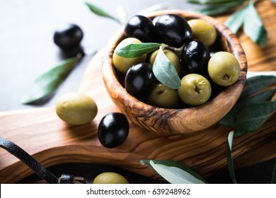 Fresh olives. Black and green olives in wooden olive bowl. Close up with copy space.