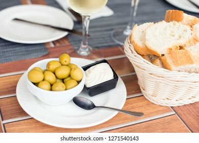 fresh olives with butter and slices of baguette