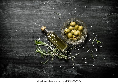 Fresh olives and the oil in the bottle with the rosemary. On black rustic background.