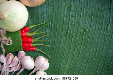 Fresh onions,garlic,red chili pepper on green banana leaf background with drop.