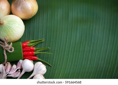 Fresh onions,garlic,red chili pepper on green banana leaf background.