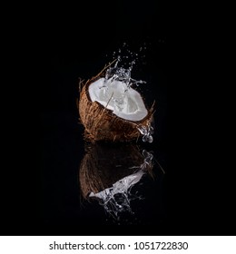 Fresh open coconut with water splash and black reflection on black background