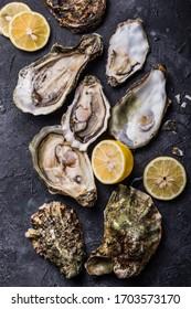 Fresh open Oysters. Healthy sea food. Dinner in restaurant. Gourmet food. Dark background. Top view