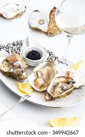 Fresh open oysters on a plate, black caviar, a lemon segment