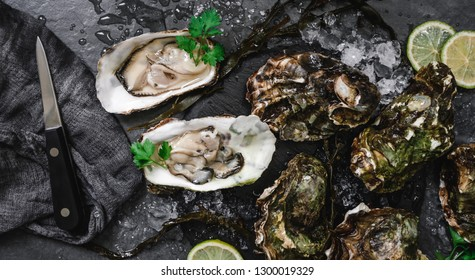 Fresh opened oysters with lemon, spices, salt, a knife and seaweed on slate stone background. Seafood, Shellfish, top view, flat lay, copy space