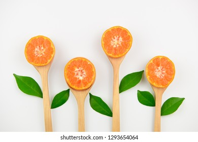 Fresh orange citrus fruit in wooden spoon and green leaves for antioxidants healthy food high in vitamin c on white background.
