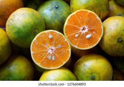 Fresh Orange cut half on pile of oranges / select focus