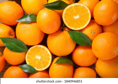 fresh orange fruits with leaves as background, top view