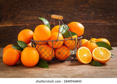 fresh orange fruits with leaves in a basket on a wooden background