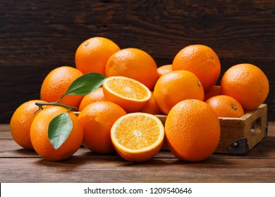 fresh orange fruits with leaves in a box on wooden table