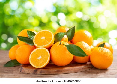 fresh orange fruits with leaves on a wooden table