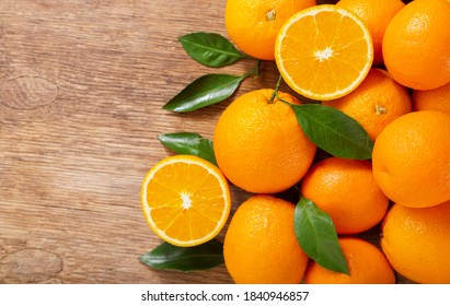 fresh orange fruits with leaves on a wooden table, top view