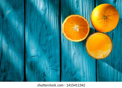 Fresh orange fruits on blue wooden board and free space for your decoration. Shadown of palme leaves and sunny day.