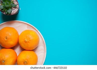 Fresh orange fruits on blue table background. Flat lay.
