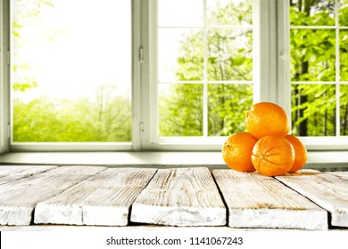 Fresh orange fruits in white wooden table and free space for your bottle or glass. Window background of summer garden landscape.