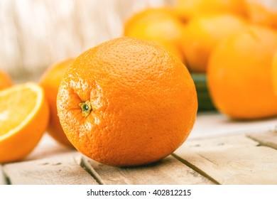 Fresh Orange, half of orange, orange lobule and basket with oranges on the wooden table on the tropic brown blurred background