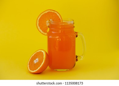 Fresh orange juice in the glass jar on yellow background