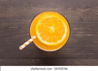 Fresh orange juice in glass on wooden background.