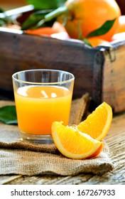 Fresh orange juice glass and oranges on rustic wood background.