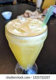 Fresh orange juice with ice in the glass on the black table in a restaurant.