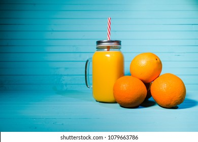 Fresh orange juice in a jar with a handle and a reusable tube on a turquoise background, copy space