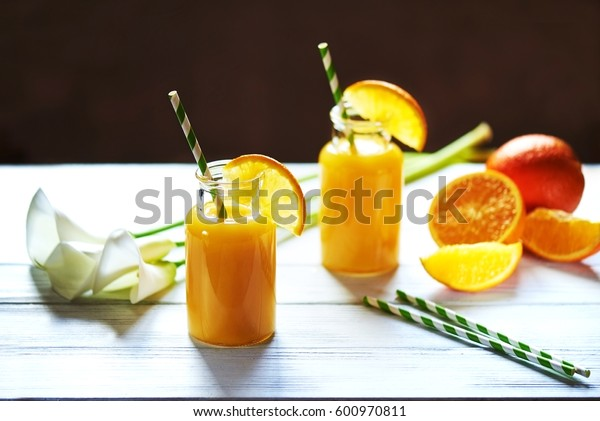 Fresh orange juice in the jar with straw and calla on white wood table. Vertical shot