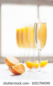 Fresh orange juice mimosas and champagne for brunch or bridal shower next to a window in natural light.  Arranged from from darkest to lightest (ombre effect with most orange juice to least).