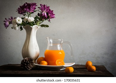 Fresh orange juice on wooden table over grunge background