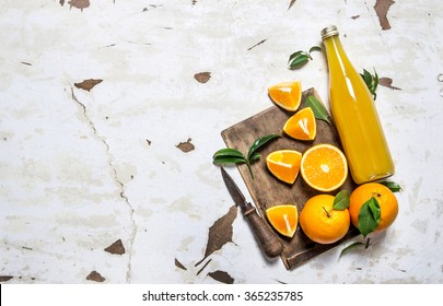 Fresh orange juice with oranges, leaves and a knife. On rustic background. Free space for text . Top view