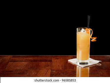 fresh orange juice and vodka in a collins glass garnished with a orange twist on a bar top
