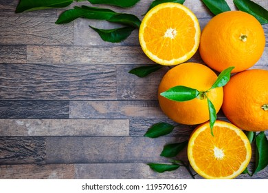 Fresh orange and leaves on wooden background.